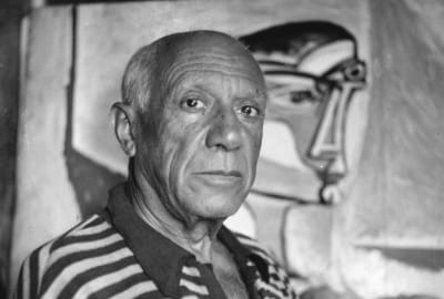 Pablo Picasso in front of one of his paintings.