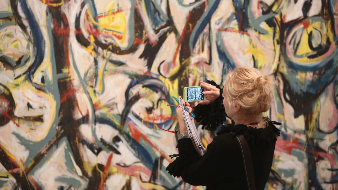 A visitor photographs 'Mural' by Jackson Pollock.