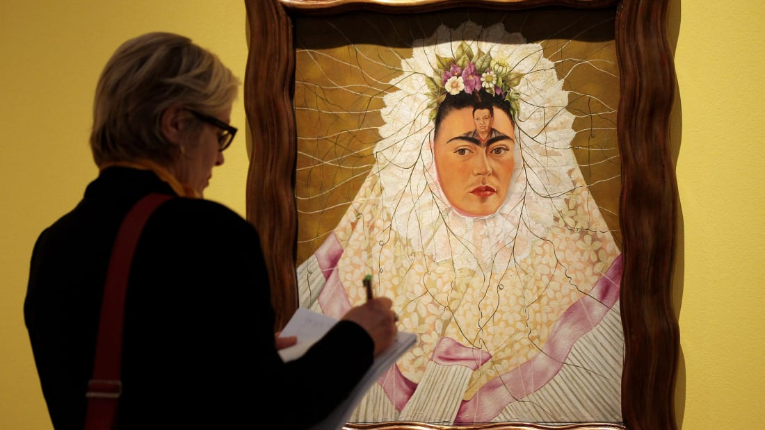 "A visitor looks at ""Self-Portrait as Tehuana or Diego on My Mind"" at the Frida Kahlo Retrospective in Berlin in 2010"