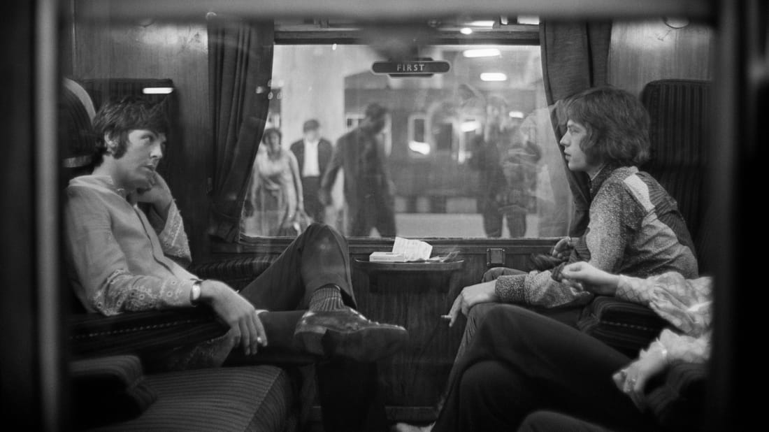 Paul McCartney of The Beatles and Mick Jagger of The Rolling Stones sit opposite each other on a train at London's Euston Station.