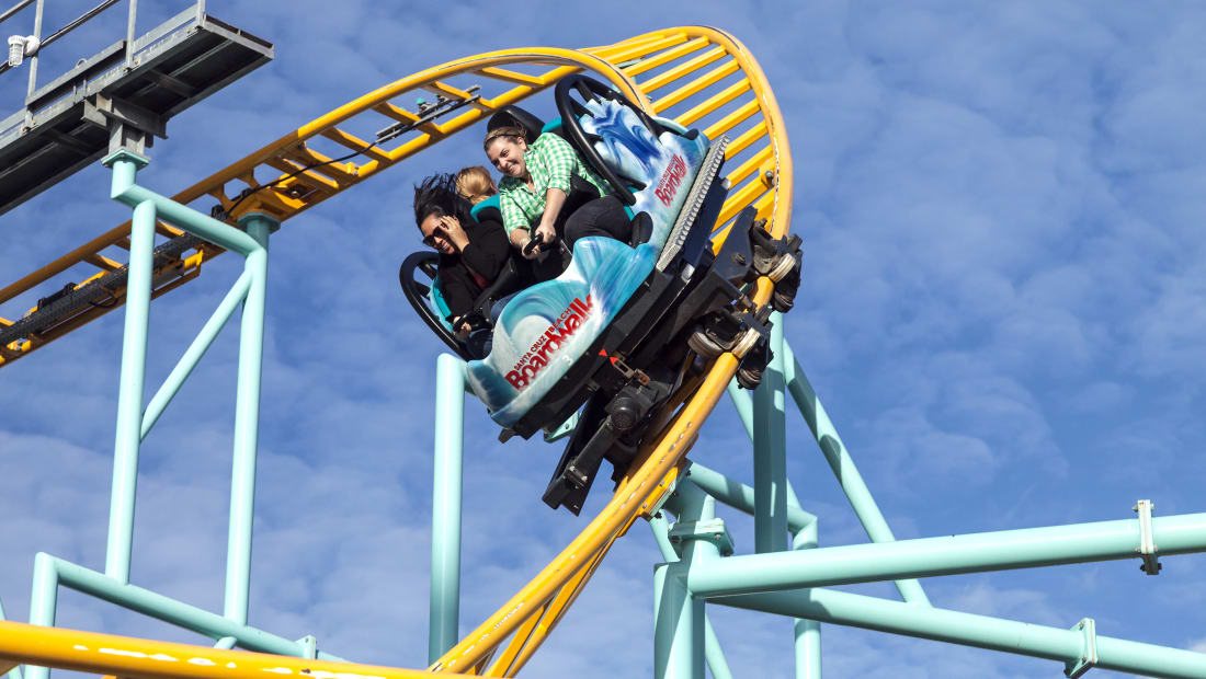 People ride a spinning roller coaster in the Santa Cruz Beach Boardwalk Park