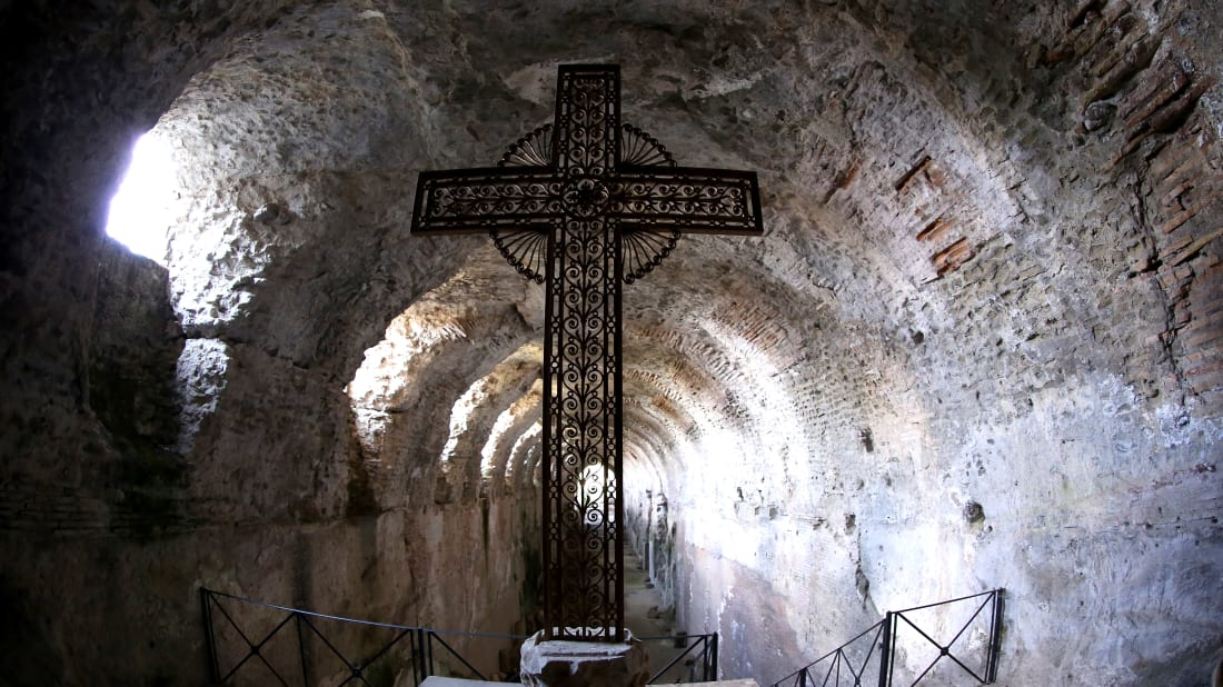 A cross stands in the Roman catacombs