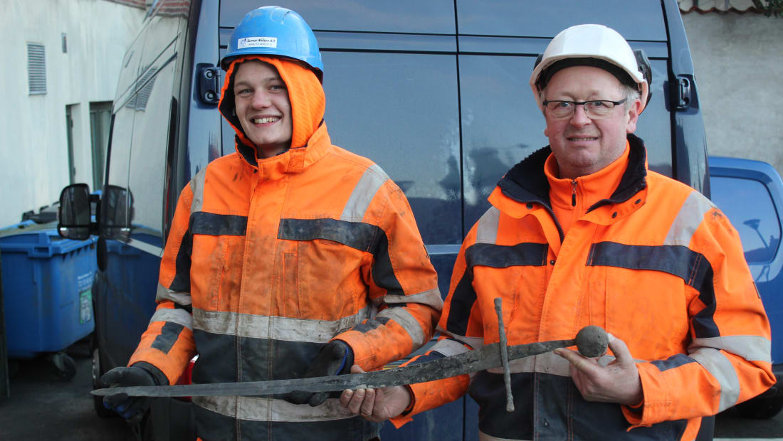 Pipe layer Jannick Vestergaard and engineer Henning Nøhr hold up the sword they found.