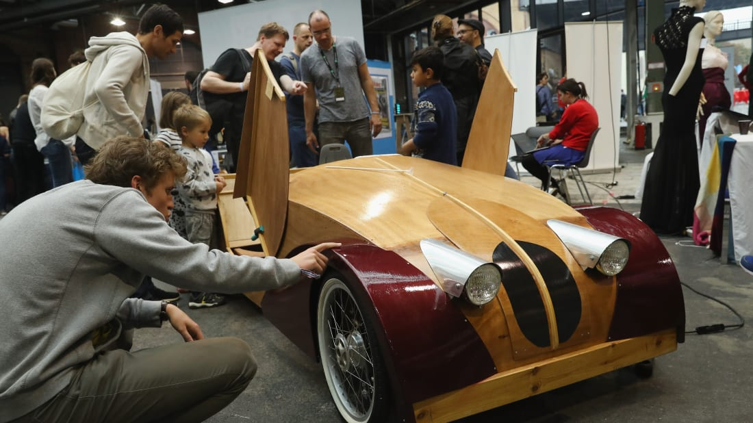 A pedal-powered wooden car is examined at the Berlin Maker Faire.