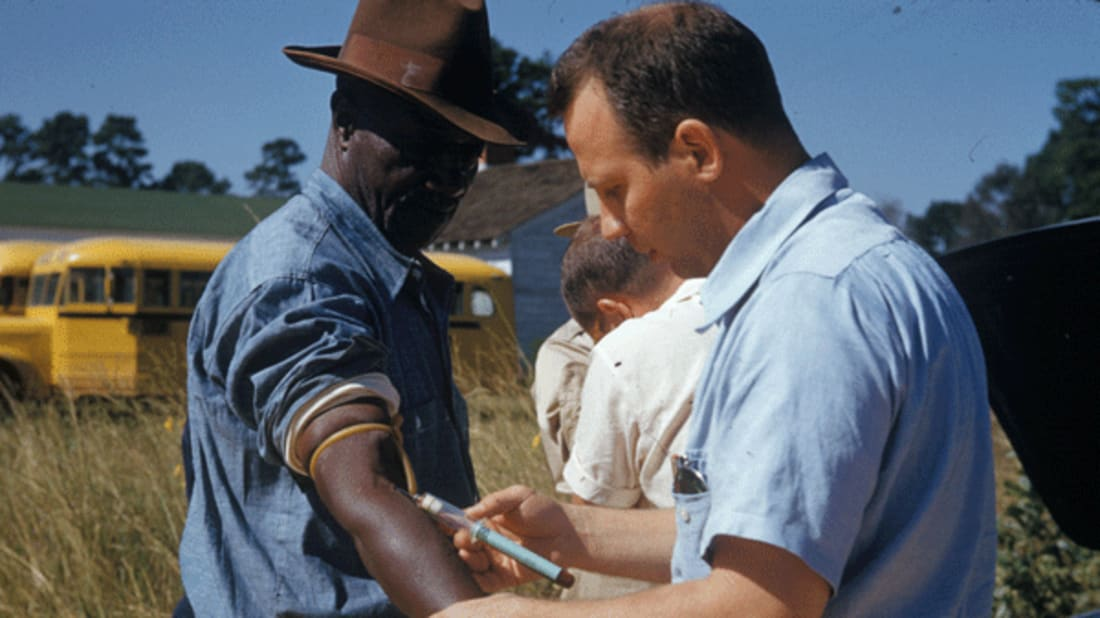 A doctor draws blood from one of the study's subjects.