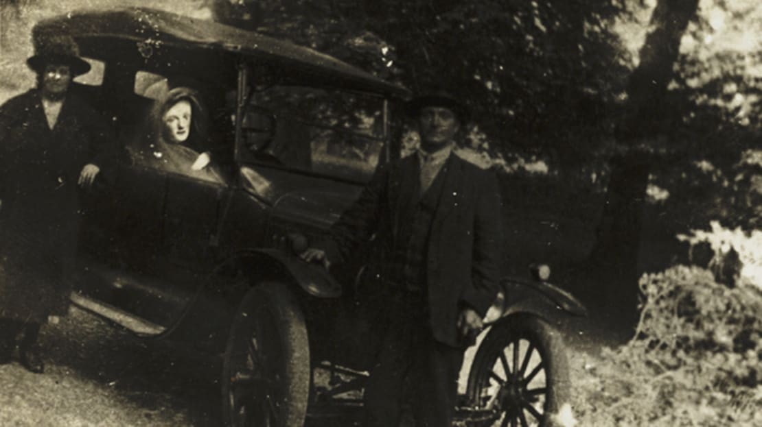 Two men pose with a spirit in their car.