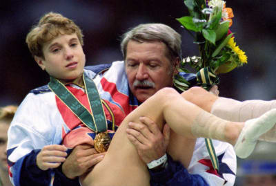 Gymnast Kerri Strug is carried off the floor by her coach Bela Karolyi after her routine at the Georgia Dome at the 1996 Olympic Games in Atlanta, Georgia on July 23, 1996.