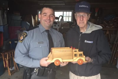 Ed Higinbotham holds a toy with Pennsylvania State Trooper Robert Broadwater.