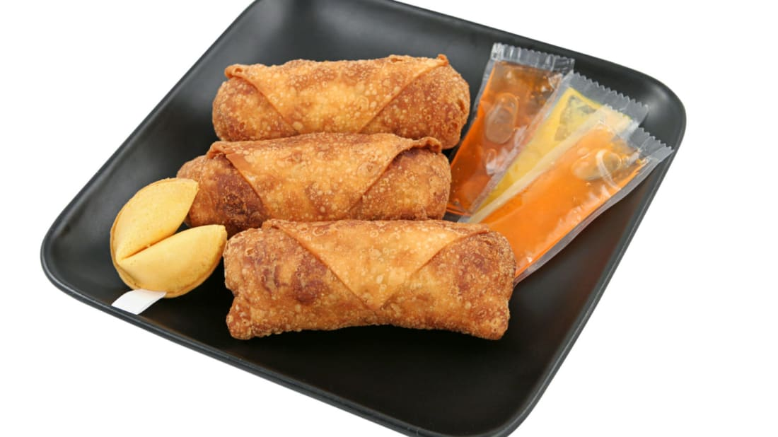 A plate of Chinese takeout with egg rolls and duck sauce