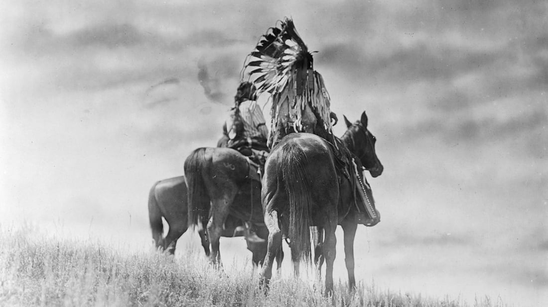 Three Cheyenne warriors on horseback.