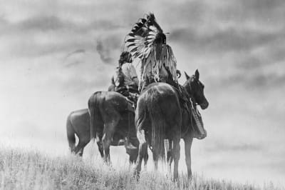 Three Cheyenne warriors on horseback.