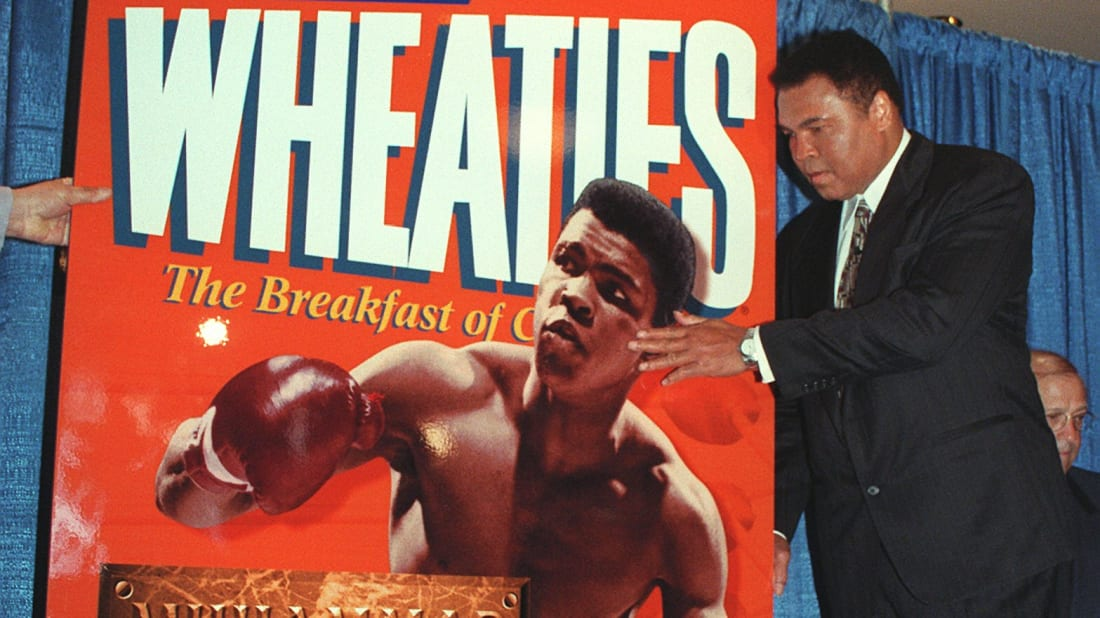Muhammad Ali touches the image of himself in his youth on this special edition Wheaties box.