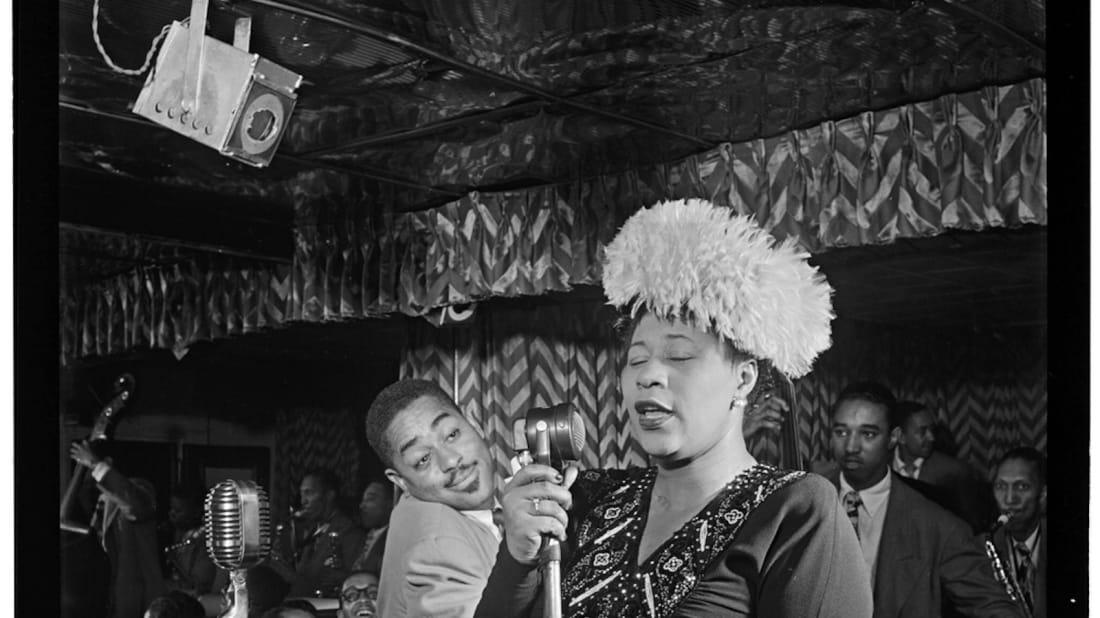 Ella Fitzgerald sings in New York City as Dizzy Gillespie looks on.
