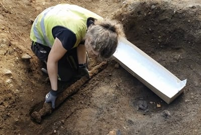 NTNU archaeologist Astrid Kviseth digs up a viking sword in Norway.