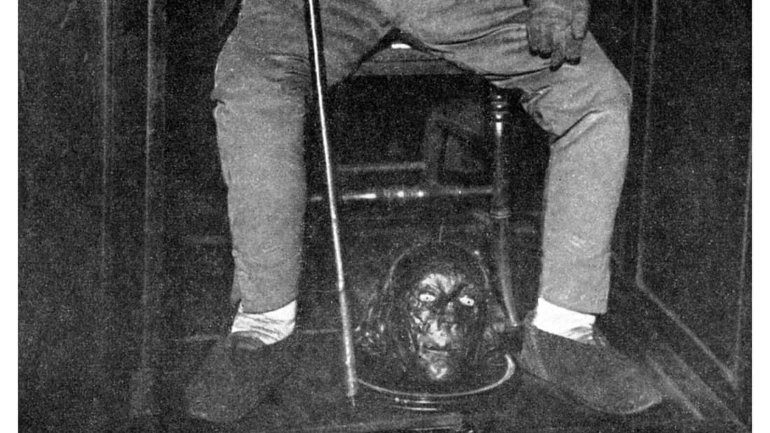 Jeremy Bentham's preserved head between the feet of his auto-icon, circa the 1950s.