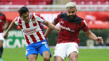 Jesús Sánchez (Chivas) compite por el esférico con el argentino Alexis Canelo (Toluca).