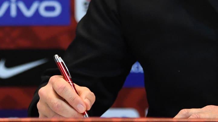 Kontrata imzayı atıyor.