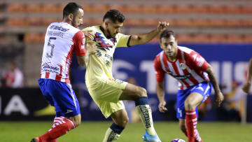 Henry Martin covers the ball in front of two Atlético de San Luis players.