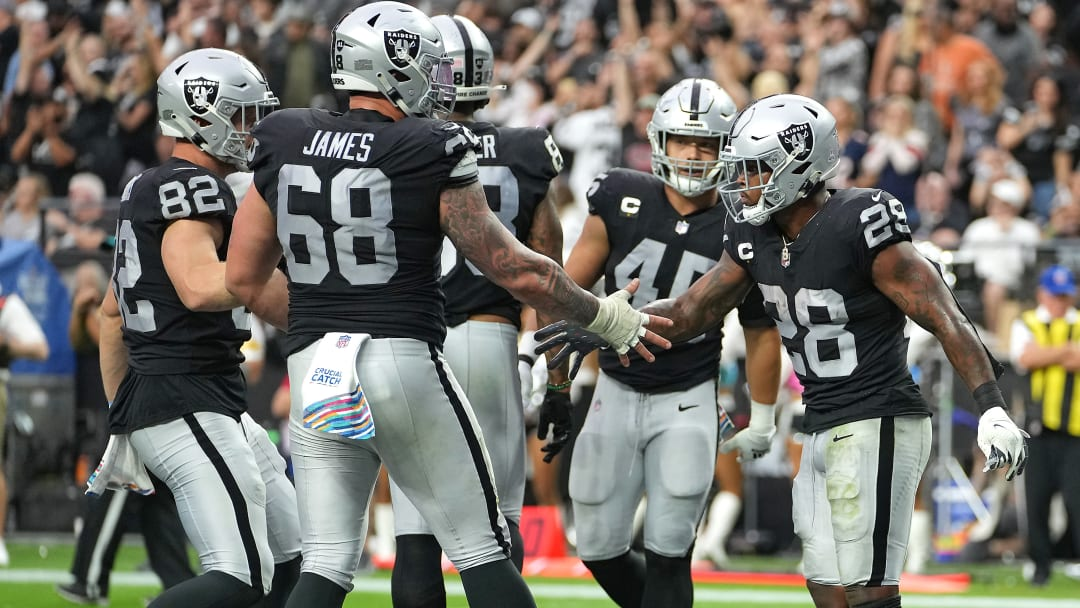 Raiders RB Josh Jacobs (28) is congratulated by Las Vegas Raiders center Andre James (68) after scoring a touchdown against the Chicago Bears.