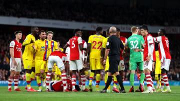 Bukayo Saka lies prone on the ground after clashing with James McArthur