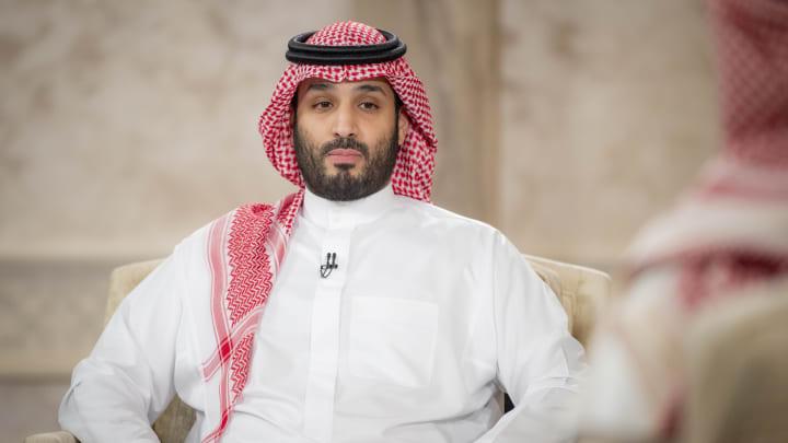 Mohammed bin Salman, sentado olhando para frente, usando camisa branca e Keffiyeh vermelha