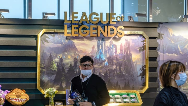A man wearing a mask stands in front of League of Legends (...