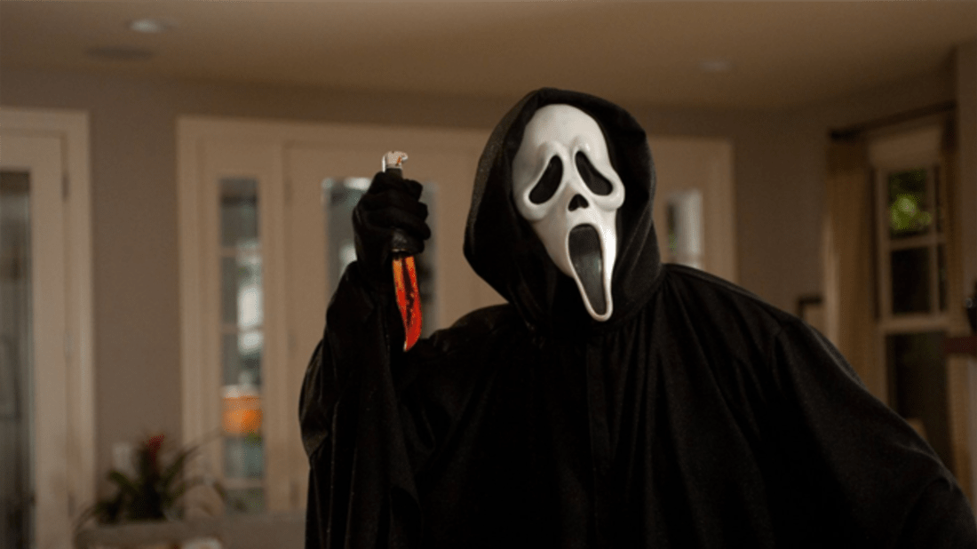 Scream (1996). A mid shot of Ghost Face, the iconic villain wearing a black cloak and hood with a white mask distorted as if screaming. He is holding a bloodied knife.