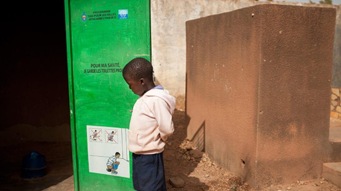 """Bill & Melinda Gates Foundation. """"Ouagadougou, Burkina Faso. A child stands by the latrines."""""""
