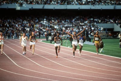 American athlete Tommie Smith, wearing black socks, celebrates after crossing the finish line of the men's 200-meter final ahead of Australian Peter Norman and compatriot John Carlos during the Mexico Olympic Games.