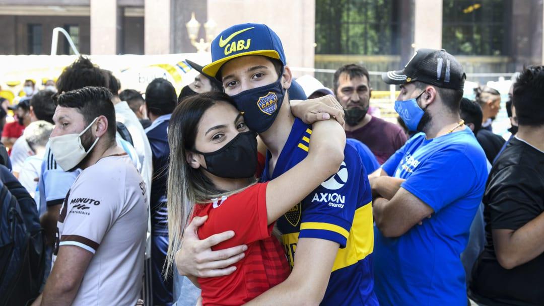 Una pareja de River y Boca se abraza en el funeral de Maradona.