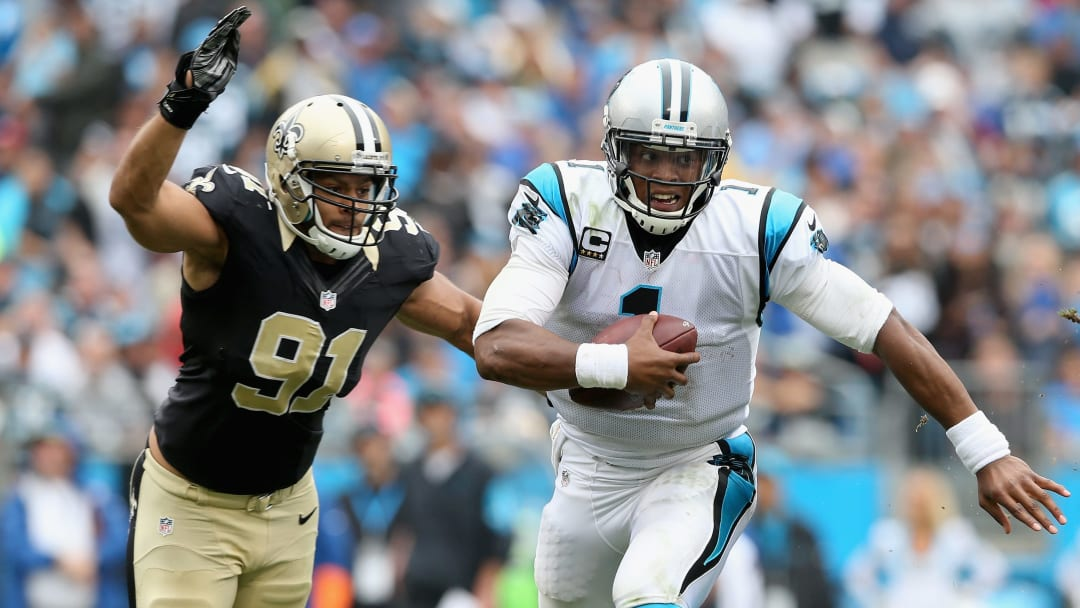 CHARLOTTE, NC - SEPTEMBER 27:   Cam Newton #1 of the Carolina Panthers runs the ball against  Kasim Edebali #91 of the New Orleans Saints in the third quarter during their game at Bank of America Stadium on September 27, 2015 in Charlotte, North Carolina.  (Photo by Streeter Lecka/Getty Images)