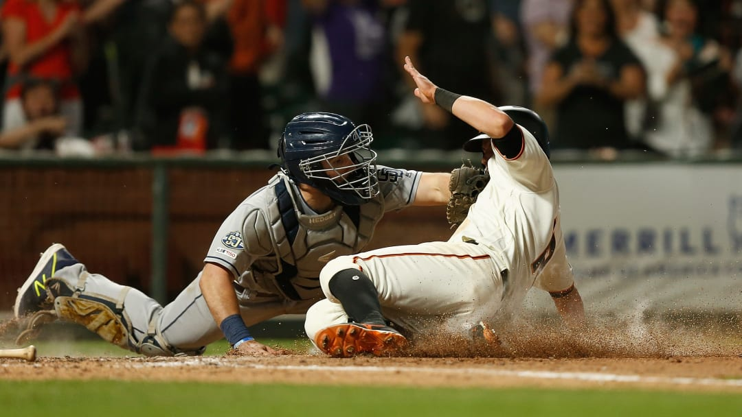 SAN FRANCISCO, CALIFORNIA - JUNE 11:  Joe Panik #12 of the San Francisco Giants slides in safe at home plate against Austin Hedges #18 of the San Diego Padres to score on a double hit by teammate Evan Longoria #10 in the bottom of the seventh inning against the San Diego Padres at Oracle Park on June 11, 2019 in San Francisco, California. (Photo by Lachlan Cunningham/Getty Images)