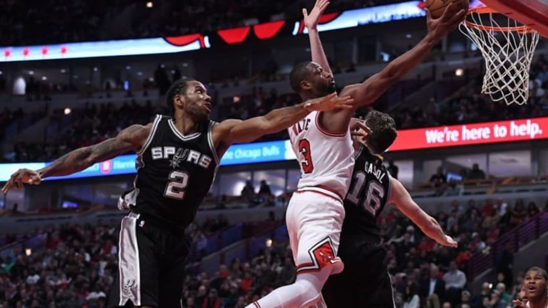 Dec 8, 2016; Chicago, IL, USA; Chicago Bulls guard Dwyane Wade (3) shoots the ball against San Antonio Spurs forward Kawhi Leonard (2) and center Pau Gasol (16) during the second half at the United Center. Chicago defeated San Antonio 95-91. Mandatory Credit: Mike DiNovo-USA TODAY Sports