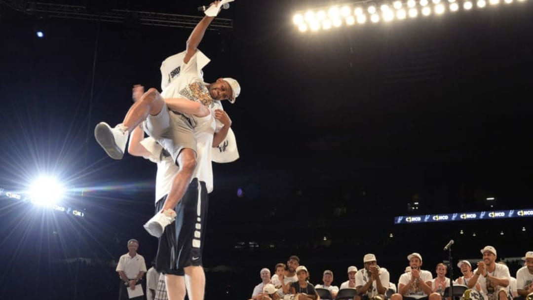 SAN ANTONIO, TX - JUNE 18: Aron Baynes #16 of the San Antonio Spurs picks up teammate Patty Mills during The San Antonio Spurs NBA Championship Celebration on June 18, 2014 in the Alamodome in San Antonio, Texas. NOTE TO USER: User expressly acknowledges and agrees that, by downloading and/or using this Photograph, user is consenting to the terms and conditions of the Getty Images License Agreement. Mandatory Copyright Notice: Copyright 2014 NBAE (Photo by D. Clarke Evans/NBAE via Getty Images)