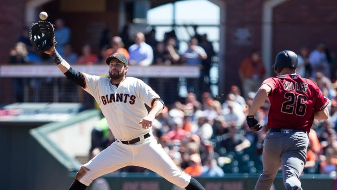 Aug 31, 2016; San Francisco, CA, USA; San Francisco Giants first baseman Brandon Belt (9) extends to catch the ball to retire Arizona Diamondbacks starting pitcher Shelby Miller (26) during the third inning at AT&T Park. Mandatory Credit: Kelley L Cox-USA TODAY Sports