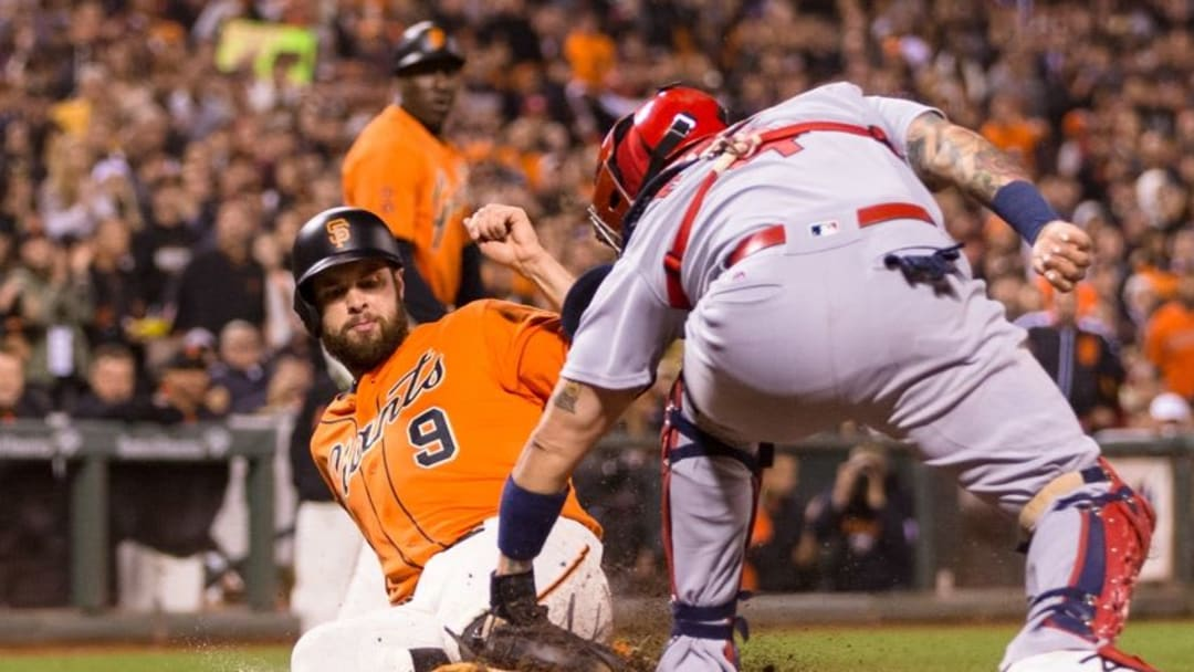 Sep 16, 2016; San Francisco, CA, USA; San Francisco Giants first baseman Brandon Belt (9) slides in safely as St. Louis Cardinals catcher Yadier Molina (4) applies a tag on a contested play in which was ruled in favor of the Giants in the third inning at AT&T Park. Mandatory Credit: John Hefti-USA TODAY Sports