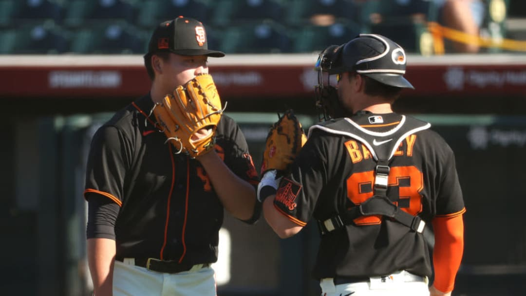 SCOTTSDALE, ARIZONA - MARCH 28: Kai-Wei Teng #82 and Patrick Bailey #93 of the SF Giants have a conversation after getting into a jam in the ninth inning against the Oakland Athletics in an MLB spring training game at Scottsdale Stadium. (Photo by Abbie Parr/Getty Images)