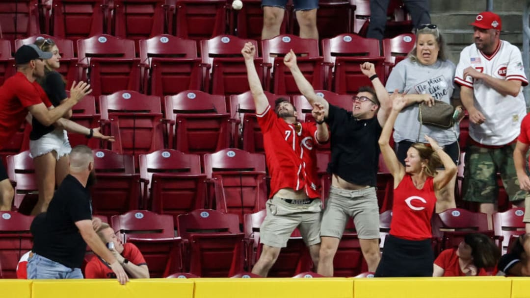 CINCINNATI, OHIO - MAY 21: Fans attempt to catch a home run hit by Jesse Winker #33 of the Cincinnati Reds. (Photo by Dylan Buell/Getty Images)