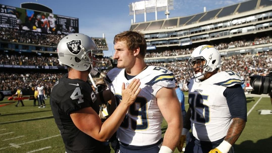 Oct 9, 2016; Oakland, CA, USA; Oakland Raiders quarterback Derek Carr (4) meets with San Diego Chargers defensive end Joey Bosa (99) after the game at Oakland Coliseum. The Raiders defeated the Chargers 34-31. Mandatory Credit: Cary Edmondson-USA TODAY Sports