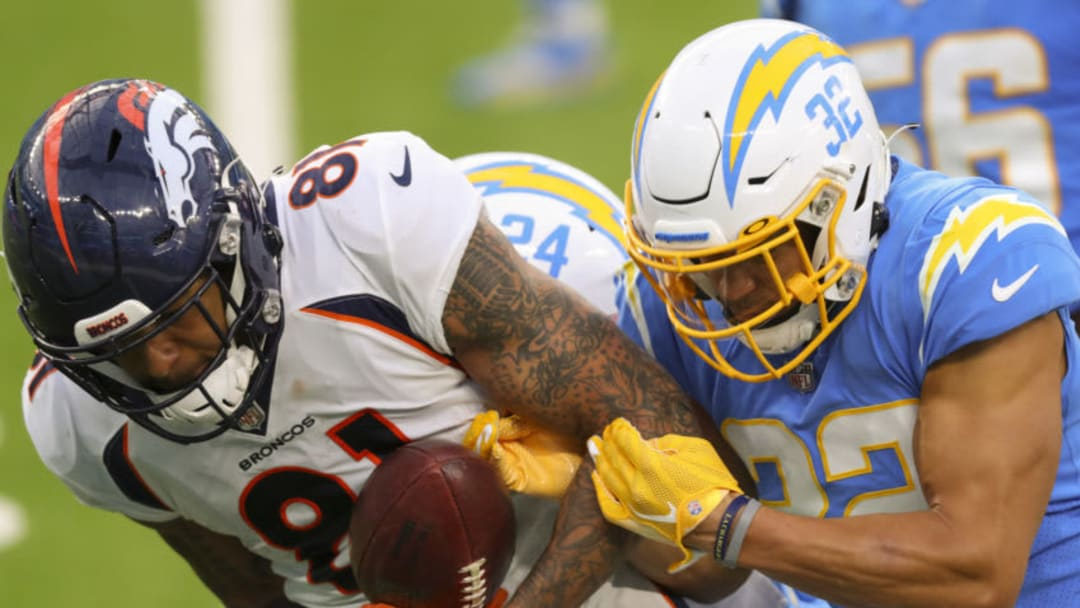 INGLEWOOD, CALIFORNIA - DECEMBER 27: Tim Patrick #81 of the Denver Broncos is tackled by Nasir Adderley #24 and Alohi Gilman #32 of the Los Angeles Chargers at SoFi Stadium on December 27, 2020 in Inglewood, California. (Photo by Joe Scarnici/Getty Images)
