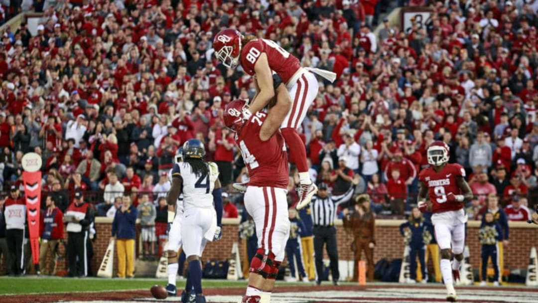 NORMAN, OK - NOVEMBER 25: Offensive lineman Cody Ford #74 and tight end Grant Calcaterra #80 of the Oklahoma Sooners celebrate a touchdown against the West Virginia Mountaineers at Gaylord Family Oklahoma Memorial Stadium on November 25, 2017 in Norman, Oklahoma. Oklahoma defeated West Virginia 59-31. (Photo by Brett Deering/Getty Images)