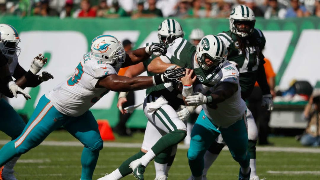 EAST RUTHERFORD, NJ - SEPTEMBER 16: Quarterback Sam Darnold #14 of the New York Jets is tackled by defensive tackle Akeem Spence #93 and defensive tackle Vincent Taylor #96 of the Miami Dolphins during the second half at MetLife Stadium on September 16, 2018 in East Rutherford, New Jersey. (Photo by Michael Owens/Getty Images)