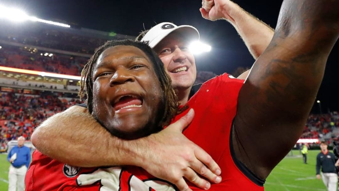 ATHENS, GEORGIA - NOVEMBER 23: Head coach Kirby Smart of the Georgia Bulldogs leaps on the back of Isaiah Wilson #79 as they celebrate their 19-13 win over the Texas A&M Aggies at Sanford Stadium on November 23, 2019 in Athens, Georgia. (Photo by Kevin C. Cox/Getty Images)