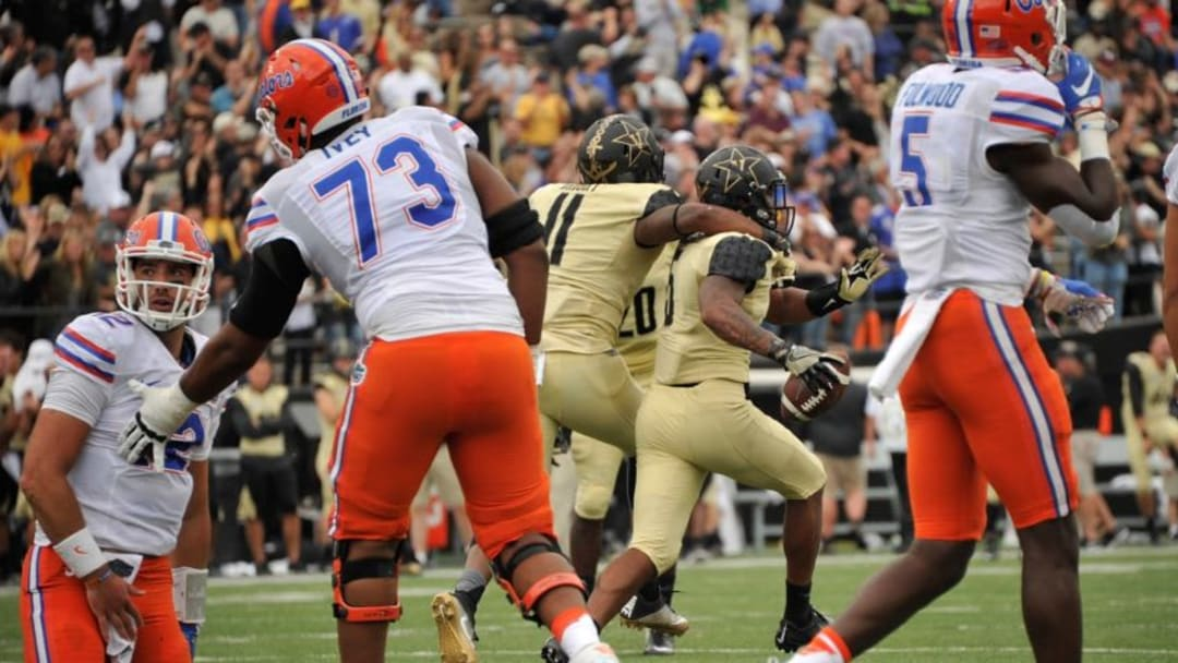NASHVILLE, TN - OCTOBER 01: Quarterback Austin Appleby #12 of the Florida Gators is helped to his feet by teammate Martez Ivey #73 as Torren McGaster #5 of the Vanderbilt Commodores celebrates recoving a fumble during the late moments of the second half at Vanderbilt Stadium on October 1, 2016 in Nashville, Tennessee. (Photo by Frederick Breedon/Getty Images)