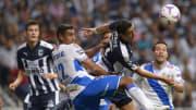 Jugadores de Rayados de Monterrey y del Puebla disputan un balón por los aires.