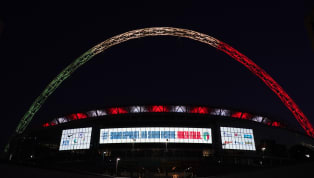 Wembley Stadium lit up Friday for a match between England and Italy that was postponed because of the coronavirus pandemic. The Three Lions were due to face...