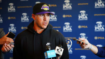 Brooks Koepka wearing a hoodie and Lakers hat.