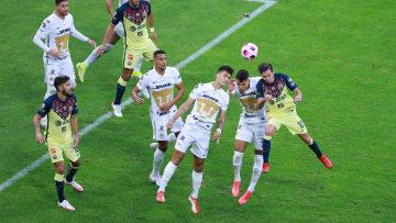 Jugadores de América y Pumas UNAM en la disputa de un balón.