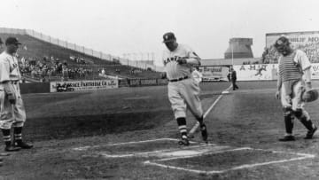 Babe Ruth reaches home plate after hitting a home run for the Boston Braves