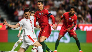 Portugal's forward Cristiano Ronaldo (C) vies with Serbia's defender Nikola Milenkovic during the Euro 2020 qualifying group B football match between Portugal and Serbia at the Luz stadium in Lisbon on March 25, 2019. (Photo by PATRICIA DE MELO MOREIRA / AFP)        (Photo credit should read PATRICIA DE MELO MOREIRA/AFP/Getty Images)